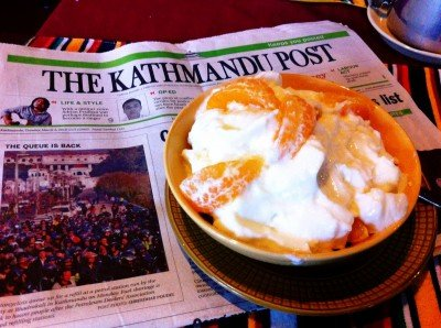 "Enjoying some juju dhau (""King Curd"") with fruit & muesli while reading the paper at Shiva Guesthouse in Bhaktapur."