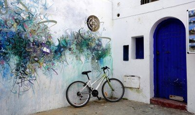 asilah morocco mural with bike and blue door